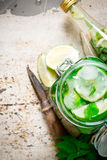 The cocktail in the jar, the bottle with ice cubes, lime, mint leaves and rum . Stock Photos