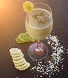 Cocktail with kiwi and banana on a black background, oatmeal, toned vegetarian royalty free stock image