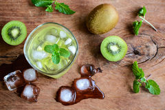 Cocktail with kiwi and mint in a glass on a wooden background Stock Photography