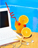 Cocktail, laptop and starfish on pool background Stock Photography