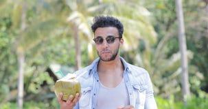 Cocktail latino-americano sobre palmeiras, latim novo de sorriso feliz Guy Tourist do coco da bebida do homem video estoque