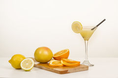Cocktail of lemon juice and vodka in a tall glass on wooden board. Cocktail of lemon juice and vodka in a tall glass, pieces of orange and lemon, grapefruit on Royalty Free Stock Photography