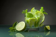 Cocktail with lime, ice and peppermint . Cocktail with lime , ice and peppermint leaves on a glass table in bar royalty free stock image