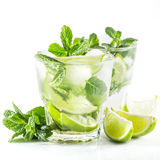 Cocktail with lime and mint on a white. Mojito cocktail with lime and mint on a white background Stock Photography