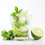 Cocktail with lime and mint on a white. Mojito cocktail with lime and mint on a white background Royalty Free Stock Image