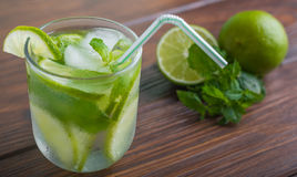 Cocktail with lime and mint on a wooden table. Mojito with lime and mint on a wooden table Royalty Free Stock Photos