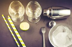 Cocktail making bar tools/Cocktail shaker, two glass lime and straws on a dark background. Top view royalty free stock images