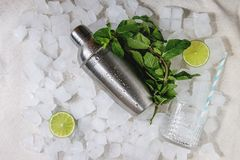 Cocktail making concept. Silver shaker, mint, sliced lime, cocktail glass with tube over crushed ice cubes. Flat lay, space royalty free stock images