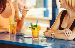 Cocktail in mano della donna sul terrazzo aperto nella barra durante l'ora legale Fotografie Stock Libere da Diritti