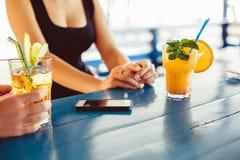 Cocktail in mano della donna sul terrazzo aperto nella barra durante l'ora legale Fotografia Stock Libera da Diritti