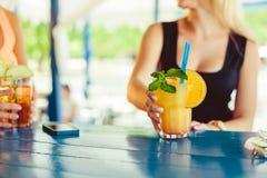 Cocktail in mano della donna sul terrazzo aperto nella barra durante l'ora legale Immagine Stock