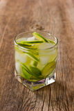 Cocktail Margarita with lemon and ice cubes in an old wooden table Stock Images