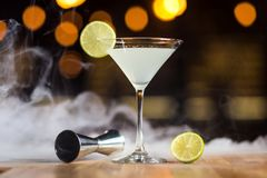 Cocktail margarita with lime standing on the bar against backgr. Ound of smoke Royalty Free Stock Photos
