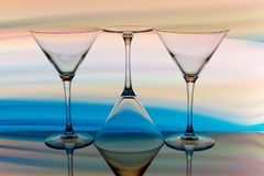 Cocktail / martini glass with a rainbow of color behind stock image