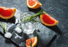Cocktail met grapefruit, ijs en rozemarijn op donkere steenachtergrond stock afbeelding