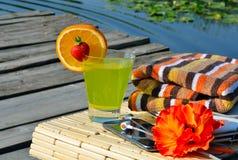 Cocktail met vruchten, laptop, celtelefoon, hoofdtelefoons en badslepen Stock Fotografie