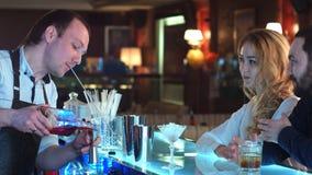 Cocktail misturado de derramamento do barman para clientes em uma barra Imagens de Stock