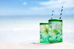 Cocktail mit Eis, Rum, Zitrone und Minze in einem Glas auf Strand Stockfoto