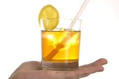 Cocktail mit Eis und Zitrone in der Hand Stockbilder