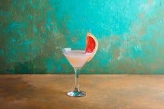 Cocktail mit Scheiben der Pampelmuse auf einem Türkishintergrund Pampelmuse Martini Stockfotografie