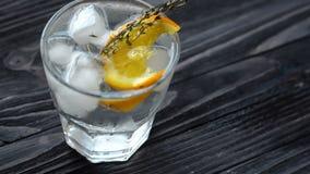 Cocktail mit Zitrusfrüchten auf dunklem Holztisch stock footage