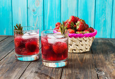 Cocktail-mocktail. Fruity cocktail drink decorated with frozen or fresh raspberry, strawberry, rosemary, ice and soda. Domestic co. Cktail with ice and rosemary Stock Photos