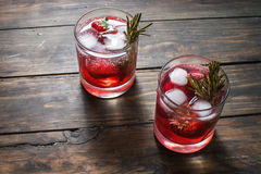 Cocktail-mocktail. Fruity cocktail drink decorated with frozen or fresh raspberry, strawberry, rosemary, ice and soda. Domestic co. Cktail with ice and rosemary Royalty Free Stock Images