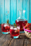 Cocktail-mocktail. Fruity cocktail drink decorated with frozen or fresh raspberry, strawberry, rosemary, ice and soda. Domestic co. Cktail with ice and rosemary Stock Photography
