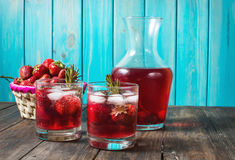 Cocktail-mocktail. Fruity cocktail drink decorated with frozen or fresh raspberry, strawberry, rosemary, ice and soda. Domestic co. Cktail with ice and rosemary Royalty Free Stock Image