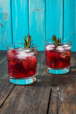 Cocktail-mocktail. Fruity cocktail drink decorated with frozen or fresh raspberry, strawberry, rosemary, ice and soda. Domestic co. Cktail with ice and rosemary Royalty Free Stock Photos