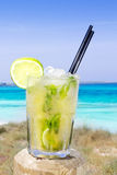 Cocktail mojito ice lemon straws in tropical beach. Mojito cocktail with ice and lemon in Balearic islands beach Stock Image