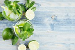 Cocktail mojito, straw and ingredients on soft shabby blue wood board, copy space, top view. Cocktail mojito, straw and ingredients on soft shabby blue wood royalty free stock photos