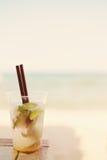 Cocktail na praia, fundo borrado de Mojito da praia Sun, embaçamento do sol, brilho imagem de stock