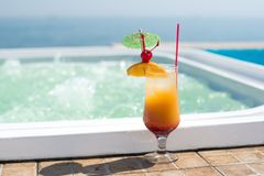 Cocktail near the swimming pool. The orange cocktail near the swimming pool Royalty Free Stock Image
