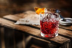 Cocktail Negroni on a old wooden board. Drink with gin, campari. Martini rosso and orange royalty free stock photos