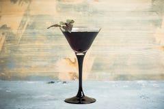 Cocktail nero di martini sui precedenti rustici Fotografie Stock
