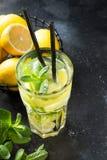 Cocktail o limonata di Mojito con calce e la menta in vetro di highball sul nero Bevanda di estate immagine stock libera da diritti