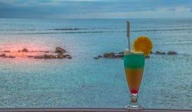Cocktail op een zonsondergangstrand royalty-vrije stock foto