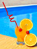 Cocktail with orange and cherry on pool background Stock Images