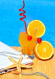 Cocktail with orange and cherry on pool background Royalty Free Stock Images