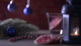 Cocktail-Pampelmuse, Kerze, Tannenzweig mit Weihnachtsspielwaren und Zuckerstangen stock footage