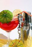 Cocktail party. Cocktail shaker and red cocktail in tall glass with umbrella Royalty Free Stock Photo