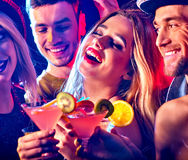 Cocktail party with group people dancing and drink cocktail. Women and men have fun in night club. Happy girl with alcohol drink on foreground stock photos