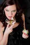 Cocktail party woman evening dress hold appetizer. Cocktail party woman in evening dress drink eat appetizer Royalty Free Stock Photography