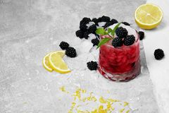 A glass of red juice and ice, juicy blackberries, green leaves of mint on a light gray background. A cocktail with pieces of ice, yellow bright slices of lemon Stock Image