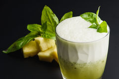 Cocktail `pineapple and basil` healthy drink. Cocktail `pineapple and basil` healthy food on a dark uniform background with pineapple and pineapple Royalty Free Stock Images