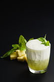 Cocktail `pineapple and basil` healthy drink. Cocktail `pineapple and basil` healthy food on a dark uniform background with pineapple and pineapple Stock Photo