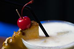 Cocktail with pineapple, cherry garnish and straw. Cocktail or punch garnished with pineapple slice and cherry with straw at the bar Stock Photo