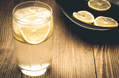 Cocktail and plate with lemons Royalty Free Stock Images