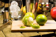 Cocktail preparation: glasses, shaker and fruits on a wooden board Royalty Free Stock Images